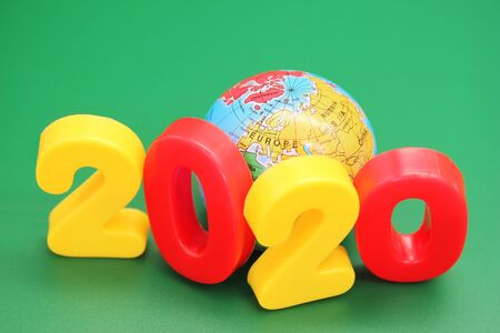 2020 new years number next to the toy globe on a green background.