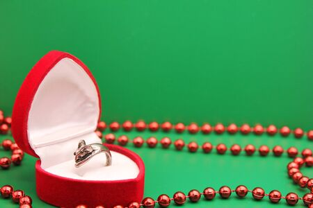 Ring in the form of a mouse in a gift red case on a green background among red Christmas beads. mouse is a symbol of The new year 2020 according to the Chinese calendar. Stok Fotoğraf