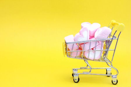 A toy cart from the supermarket is filled with marshmallows in the shape of hearts. Yellow background. The concept of love and Valentine's Day. Copy Space.