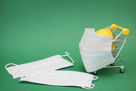 A medical mask is placed on a shopping cart containing a fresh lemon. Two medical masks lie near them. Protection against viruses and infections.