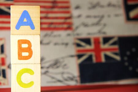 ABC-letters of the English alphabet on wooden cubes on the background of images of the English flag. Learning foreign language. English for beginners.