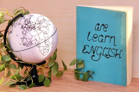 The book We learn English beside a globe and a potted plant. Study English language. 版權商用圖片