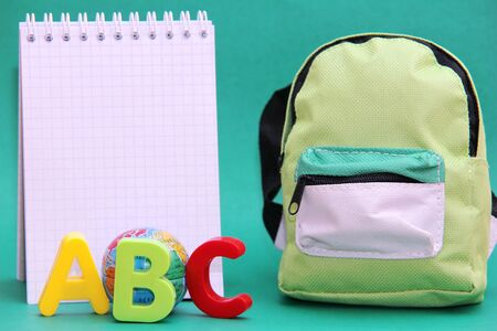 ABC-colored letters of the English alphabet next to a toy globe and a Notepad. School bag. Back to school.