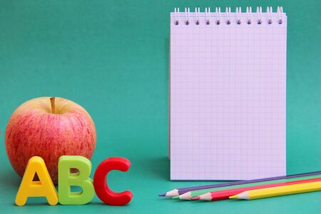 English ABC alphabet letters next to apple. Colored pencils and an empty Notepad page Learning foreign language.