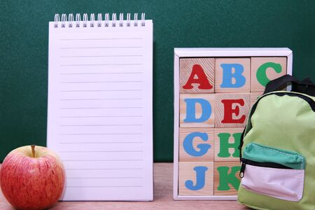 Wooden blocks with letters of the English alphabet , notebook and the apple next to them. Back to school. 版權商用圖片