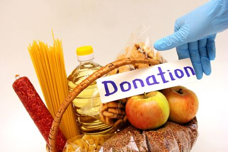 A hand in a rubber glove holds the inscription Donation in the basket with a food . Social assistance with food. Banco de Imagens