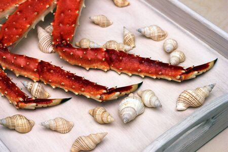 Legs of a boiled crab on a wooden tray among the shells. Delicious Seafood. Imagens