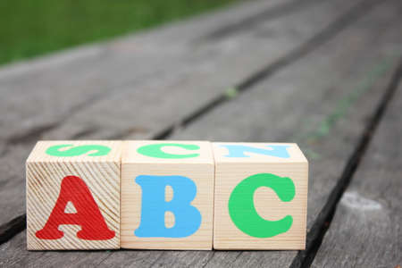 ABC -the first letters of the English alphabet on wooden toy blocks which are on the old boards in the outdoor. Learning foreign language. English for beginners. 写真素材