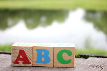 ABC -the first letters of the English alphabet on wooden toy blocks which are on the old boards in the outdoor near the lake . Learning foreign language. Stok Fotoğraf