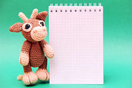 The bull is the symbol of the New year 2021. A knitted brown toy bull next to a Notepad . Copy Space.