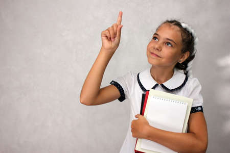 A girl with books in her hands points up with her hand and index finger. Stok Fotoğraf