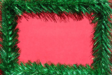 Christmas frame made of green tinsel on a red background. Copy space. Empty space for text. Blank for an online Christmas card.