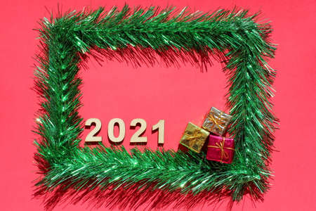 Christmas frame made of green tinsel on a red background. Copy space. Empty space for text. Preparation for an online Christmas card with 2021 new years number. Stok Fotoğraf