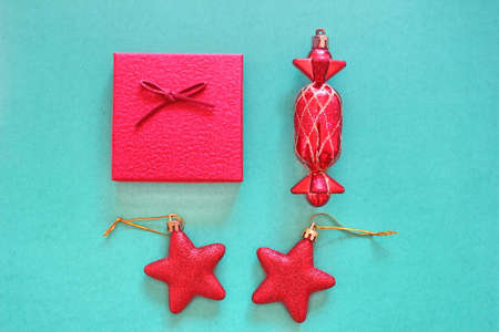 Christmas flatlay. Red Christmas toys and a red gift box are placed on a green background. The view from the top.