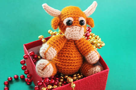 The bull is a symbol of the New year 2021. A toy knitted bull is in a red box with Christmas beads on a green background.