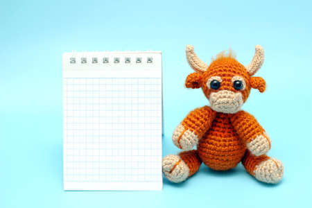 The bull is the symbol of the New year 2021. A knitted brown toy bull next to a Notepad on a blue background. Copy Space. Stok Fotoğraf