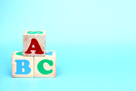 ABC -the first letters of the English alphabet on wooden toy blocks on a blue background. Learn foreign languages. English for beginners. Copy space.