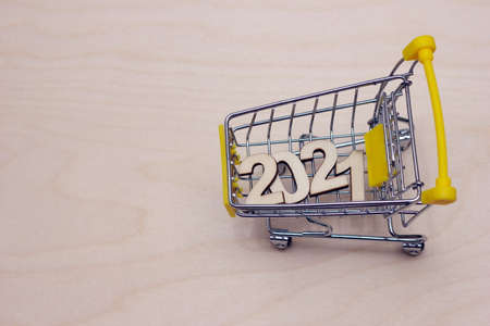 The numbers 2021 in a supermarket toy cart on a wooden background. Happy New year. Stok Fotoğraf