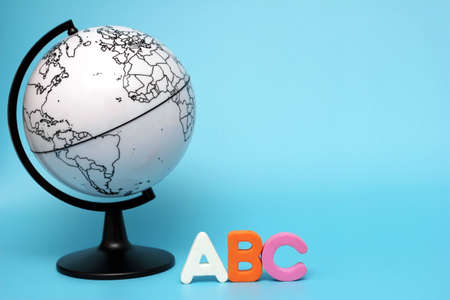 English ABC alphabet letters next to black and white globe. Learning foreign language. English for beginners. International language.