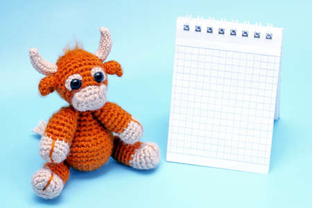 Toy bull. The bull is the symbol of the New year 2021. A knitted brown toy bull next to a Notepad on a blue background.