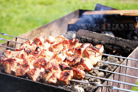 Meat skewers on skewers are grilled in the open air. Picnic concept