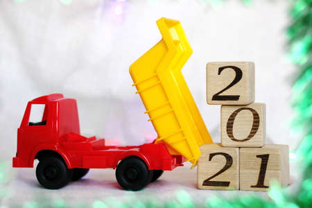 2021 new years number on wooden blocks that are unloaded by a toy dump truck. Happy New year.