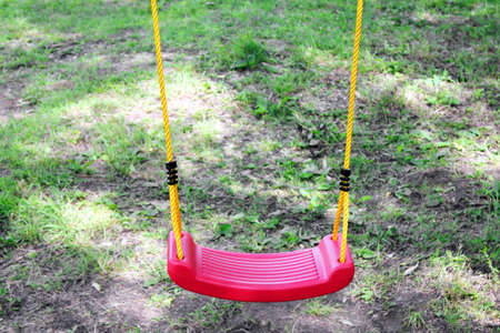 Empty childrens red plastic swing on yellow ropes. No one. Childhood and loneliness concept.