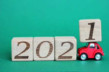 A red toy car carries blocks with the numbers 2021. The new year 2021 is approaching. Happy New year. Copy space. Stok Fotoğraf