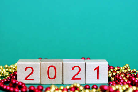 New years number 2021 in red numbers on wooden blocks among Christmas beads. Happy New year. Stok Fotoğraf
