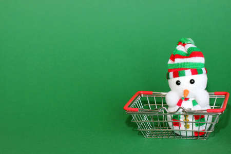 A toy Christmas Snowman is in a metal shopping basket from the supermarket. Preparing for the New year. New years shopping concept. Stok Fotoğraf