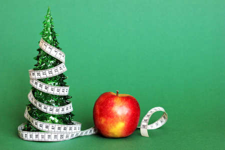 A centimeter-long ribbon is wrapped around a small green toy Christmas tree next to an Apple. The concept of healthy and healthy food during the Christmas holidays. The concept of weight loss .