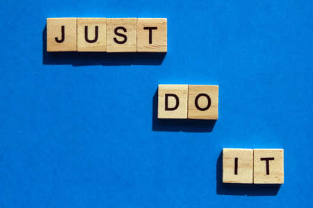 Just do it - the motivating inscription is laid out on a blue background with wooden blocks with black letters. Call to action. Motivation for everyone.