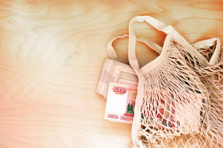 A bundle of Russian banknotes with a face value of 5000 rubles is in an eco-friendly knitted bag for purchases. Zero waste. Savings due to reusable packages and bags. Stok Fotoğraf