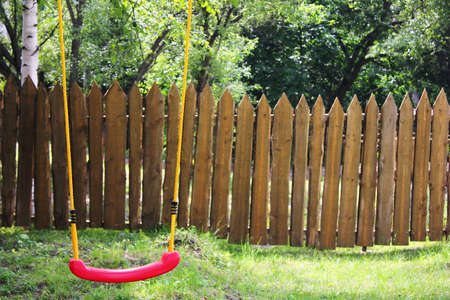 Empty childrens red plastic swing on yellow ropes. No one. Childhood and loneliness concept. Life in the country.