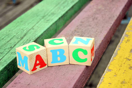 ABC -letters of the English alphabet on wooden toy blocks which are on the old boards in the outdoor. Learning foreign language. Concept of education.