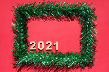 Christmas frame made of green tinsel on a red background. Copy space. Empty space for text. Christmas card with 2021 new year's number. Stok Fotoğraf