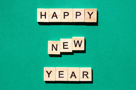 Happy New Year - an inscription made in black letters on wooden blocks . Green background. Holiday concept Stok Fotoğraf