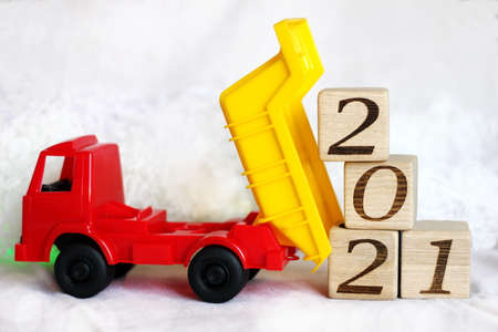 2021 new years number on wooden blocks that are unloaded by a toy dump truck on white background. Happy New year.