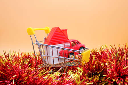A toy house and a red toy car in a small shopping cart among Christmas tinsel. Concept of Christmas and new year gifts and purchases. Christmas and new Year shopping.