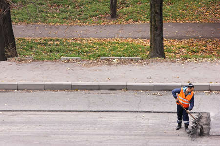 Russia, Vladivostok October 21, 2020: A road worker in an orange vest removes old asphalt with a shovel. Road works to replace asphalt. Maintenance of the roadway. The view from the top. Editöryel