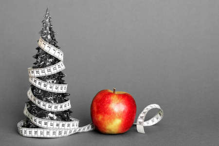 A centimeter-long ribbon is wrapped around a small toy Christmas tree next to a ripe apple. The concept of healthy and healthy food during the Christmas holidays. The concept of weight loss.