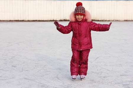 Happy girl rides in the winter on the ice rink on skates. Figure skating training. Winter sports and winter entertainment concept. Winter break is here.