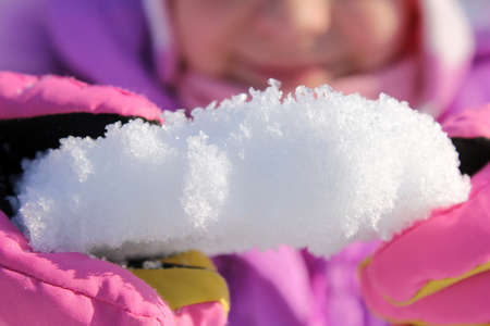 A piece of snow in the hands of a child. Close up. Winter has come. Winter time. Stok Fotoğraf
