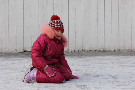 The girl in skates is sitting on a rink on the ice. Winter sports and winter entertainment concept. Winter break is here.