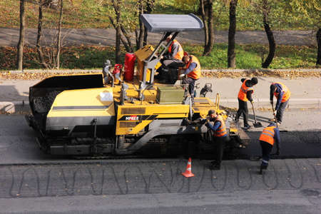 Russia, Vladivostok, October 21, 2020: paver and road workers in orange vests. Road works to replace asphalt. Maintenance of the roadway. Patching.