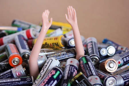 Vladivostok, Russia - 5 November, 2020: Plastic hands are raised up from a pile of old batteries of different brands. The concept of ecology.