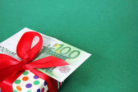 100 Euro banknote on a gift box with a red bow. Green background. The concept of a holiday and cash gifts. Stok Fotoğraf