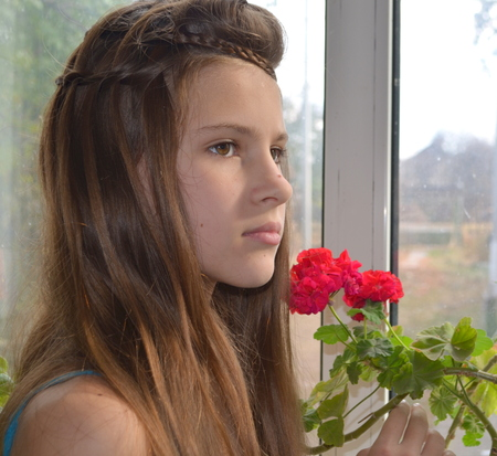 The girl near the window with geraniums