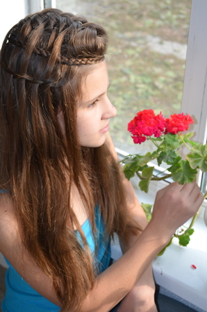 originative: The girl near the window with geraniums