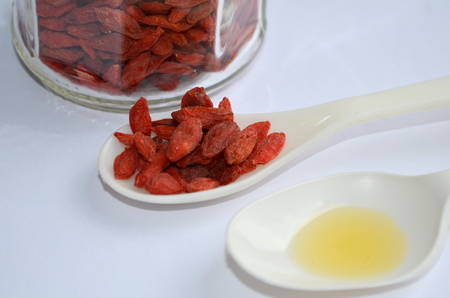 longevity medicine: Oil with goji berries on a white background